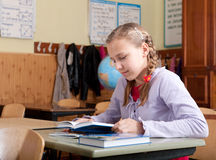 Cute girl reading book in classroom at school Stock Photos