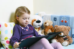 Cute girl reading a book on her bed with toys around her Stock Photography