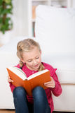 Cute Girl Reading Book At Home Royalty Free Stock Photos