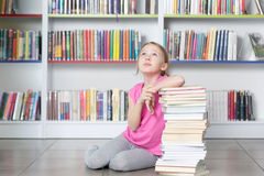 Cute girl reading book in library Royalty Free Stock Photos