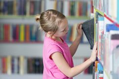 Cute girl reading book in library Royalty Free Stock Photography
