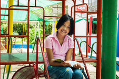 Cute  girl reading book at playground Royalty Free Stock Photos