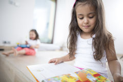 Cute girl reading book with sister in background at home Stock Image