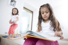 Cute girl reading book with sister playing in background at home Royalty Free Stock Images