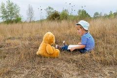 Cute girl reading book Teddy bear Royalty Free Stock Image