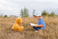 Cute girl reading book Teddy bear Royalty Free Stock Images