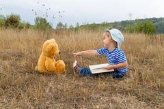 Cute girl reading book Teddy bear Royalty Free Stock Photo