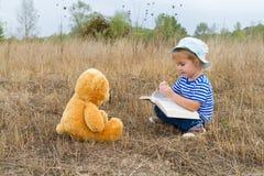Cute girl reading book Teddy bear Stock Photography