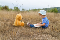 Cute girl reading book Teddy bear Stock Image