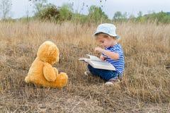 Cute girl reading book Teddy bear Royalty Free Stock Photos
