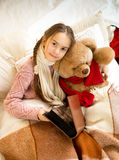 Cute girl reading book to teddy bear at bed Royalty Free Stock Photo