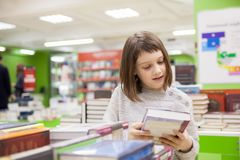 Cute girl reading books at store. Portrait of girl of 8 years choosing books in bookstore stock images