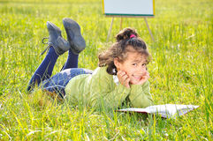 Cute girl reading on meadow with board behind Royalty Free Stock Image
