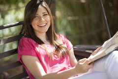 Cute girl reading outdoors. Gorgeous young woman reading a book outdoors Stock Photo