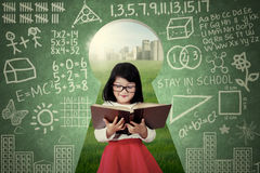 Cute girl reads book on the keyhole Royalty Free Stock Photo