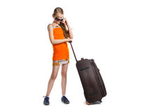 Cute girl ready for summer vacation. Joyful girl with luggage bag about to travel. Isolation on a white background Stock Images
