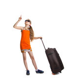 Cute girl ready for summer vacation. Joyful girl with luggage bag about to travel. Girl in sunglasses looks up and points a finger. Isolation on a white Royalty Free Stock Photos