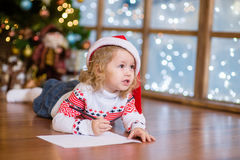 Cute girl in red Christmas hat writing a letter to Santa Claus.  Royalty Free Stock Image