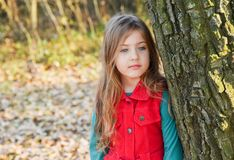 Cute girl in red dress stands next to the big tree stock images