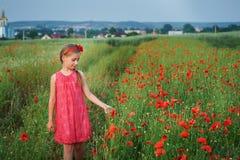 Cute girl in red dress walks at poppy field Stock Photo
