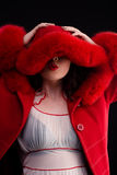 Cute girl in red fur coat Stock Photography