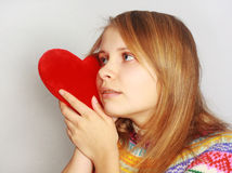 Cute girl with red fur heart. Cute blonde girl pressing red fur heart to her cheek isolated on light grey background Royalty Free Stock Images