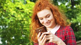Happy cute girl with red hair typing message on smartphone sitting in park. Cute girl with red hair sitting in green park and texting on smartphone. Low angle of stock video footage