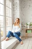 Cute girl with red hair sitting on sunny window Stock Photography