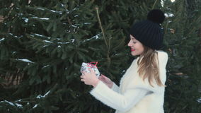 Cute girl with red lips comes to fir-tree and takes a festive gift from a branch stock video footage