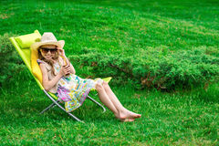 Cute girl relaxes with juice  at chair on grass. Royalty Free Stock Photography