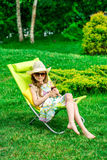 Cute girl relaxes with juice  at chair on grass. Royalty Free Stock Image