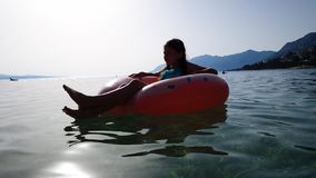 Cute girl relaxing on inflatable mattress in blue sea