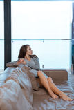 Cute girl is relaxing on leather sofa Royalty Free Stock Images