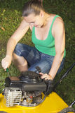Cute girl repairing  yellow lawn mower Stock Photography