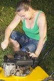 Cute girl repairing  yellow lawn mower Stock Photography