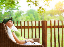 Cute girl resting on veranda. Young traveler woman sleeping on backyard in sanatorium, relaxation outdoors, luxury resort, pleasure concept Royalty Free Stock Photos