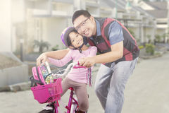 Cute girl rides a bike with dad near the house Stock Images