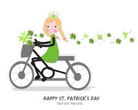 Cute girl riding a bicyle with Happy St. Patrick's Day Royalty Free Stock Photography