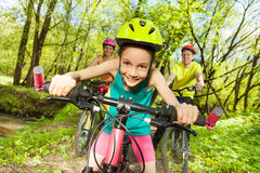 Cute girl riding her mountain bike in the park. Cute girl in bicycle helmet, riding her mountain bike in the sunny spring park Royalty Free Stock Photo