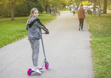 Cute girl riding her scooter on a paved pathway outdoors Royalty Free Stock Images