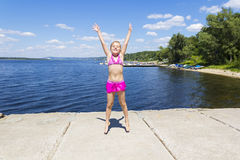 Cute girl on the riverbank in pink swimsuit Royalty Free Stock Image
