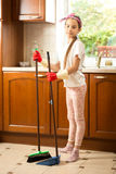 Cute girl in rubber gloves sweeping floor at kitchen with swab Royalty Free Stock Photo