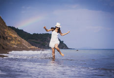 Cute girl is runing along the beach Stock Image