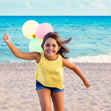 Cute girl running on beach with balloons. Stock Photo
