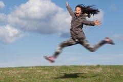 Cute girl running jumping stock photography