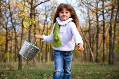 Cute girl running with a tin bucket outdoors Stock Images