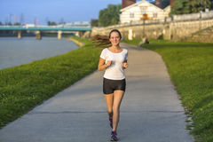 Cute girl running on treadmill along river in the big city in the evening. Stock Photos