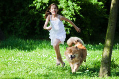 Cute girl runs with her dog Stock Images