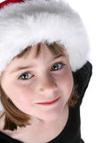 Cute girl's face and eyes; wearing Santa hat Stock Photo