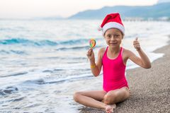 Cute girl in santa claus hat and lollipop on the beach, free space. Christmas background. Winter holidays in tropical countries. Thumbs up stock image